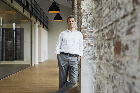 Portrait of confident businessman leaning against brick wall in modern office - PDF01474