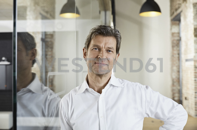 Portrait of smiling businessman leaning against glass pane - PDF01480