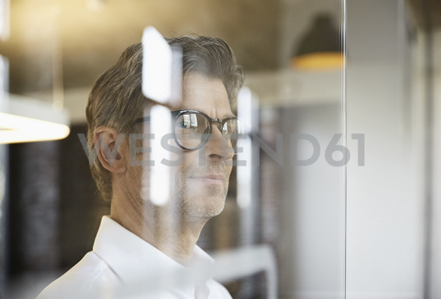 Mature businessman wearing glasses looking out of window - PDF01483