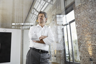 Portrait of mature businessman leaning against glass pane in modern office - PDF01489