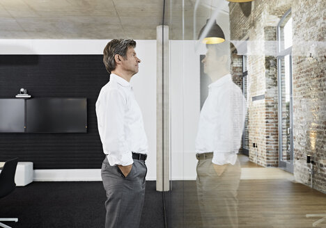 Mature businessman reflecting in glass pane of modern conference room - PDF01492