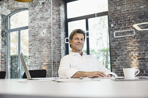 Portrait of mature businessman with laptop in modern office - PDF01504