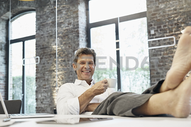 Barefooted businessman relaxing and drinking coffee in modern office - PDF01507