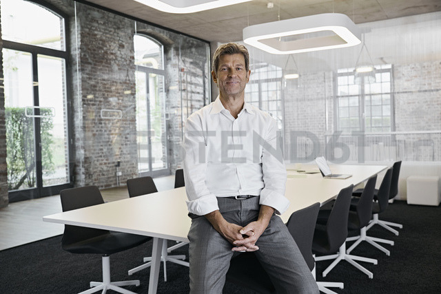 Portrait of confident mature businessman in conference room of modern office - PDF01513