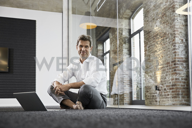 Portrait of barefoot businessman with laptop on floor in modern office - PDF01519