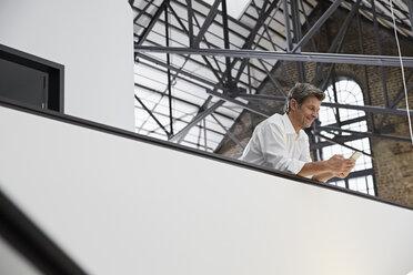 Mature businessman using smartphone in modern office - PDF01522