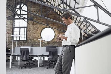 Mature businessman using smartphone in modern office - PDF01525