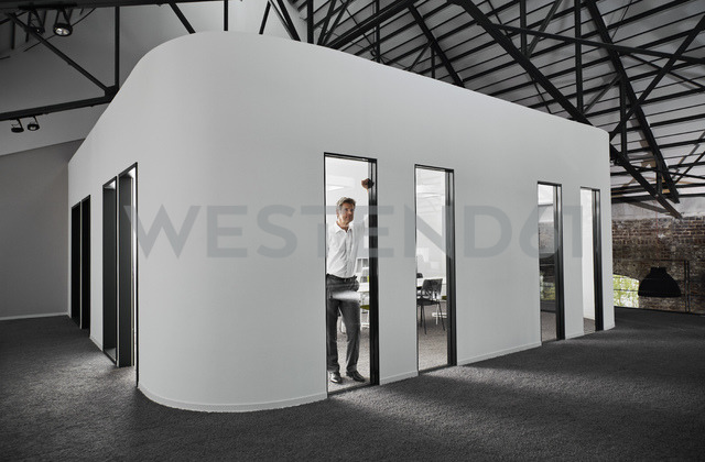 Businessman in modern conference room looking out of window - PDF01531