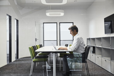 Mature businessman in modern conference room using laptop - PDF01534