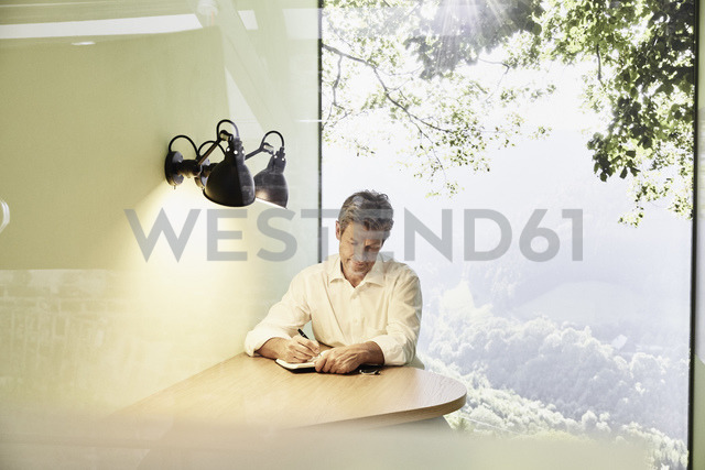 Businessman writing in book at table in modern office with panorama window - PDF01537