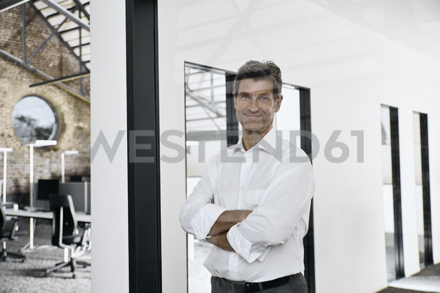 Portrait of smiling mature businessman in modern office - PDF01543