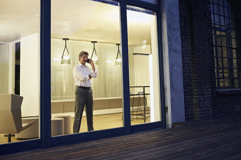 Exterior view of man using smartphone in modern building at night - PDF01552