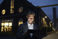 Smiling businessman using tablet outside modern building at night - PDF01555