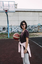 Young woman standing with basketball on outdoor court - VPIF00325
