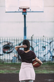 Rear view of young woman standing with basketball on outdoor court - VPIF00328