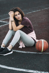 Portrait of young woman sitting with basketball on outdoor court - VPIF00331