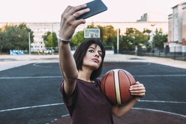 Young woman with basketball taking a selfie on outdoor court - VPIF00334