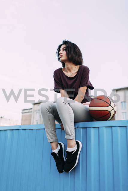 Young woman with basketball sitting on container - VPIF00337