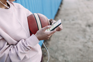 Close-up of woman with basketball, smartphone and earphones - VPIF00340