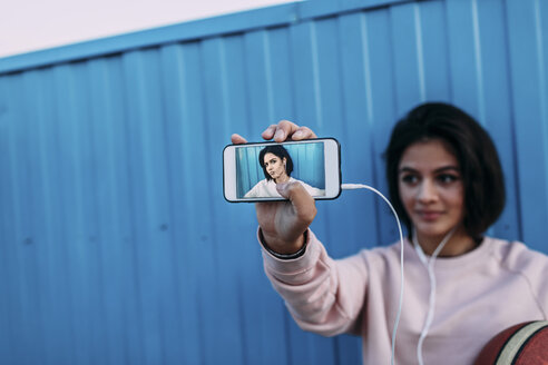 Young woman with basketball showing a selfie at container - VPIF00343