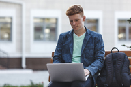 Redheaded young man sitting on bench using laptop - VPIF00349