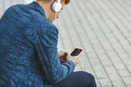 Young man sitting outdoors with smartphone and headphones - VPIF00355