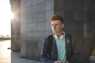 Redheaded young man outdoors with headphones - VPIF00358