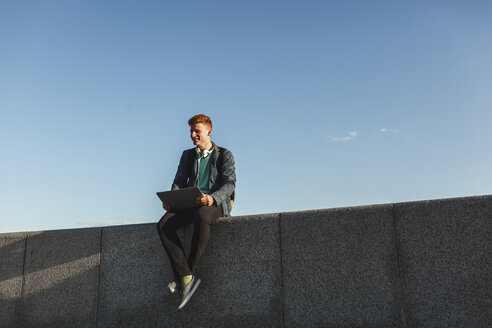 Smiling redheaded young man sitting on wall with laptop - VPIF00364