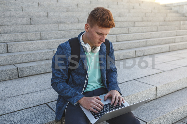 Redheaded young man sitting on stairs using laptop - VPIF00367