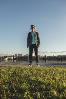 Redheaded young man standing outdoors with headphones - VPIF00370