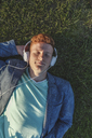 Redheaded young man with headphones lying on grass - VPIF00373