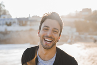 Portrait of laughing young man with stubble on the beach at sunset - AFVF00136