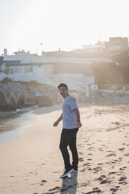 Happy young man strolling on the beach at sunset - AFVF00139