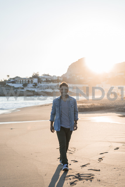 Happy young man strolling on the beach at sunset - AFVF00145