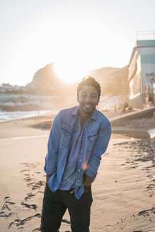Portrait of smiling young man on the beach at sunset - AFVF00148
