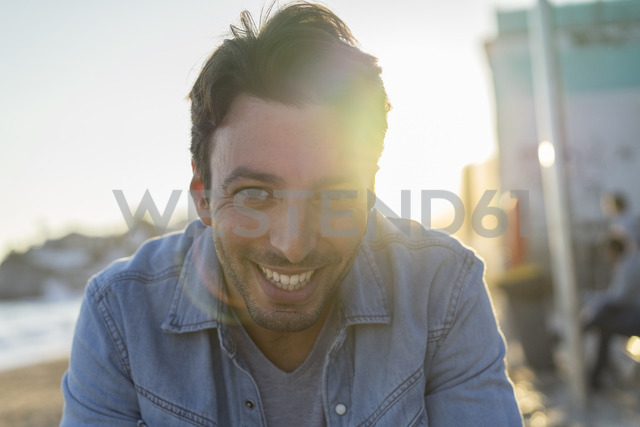 Portrait of laughing young man on the beach at sunset - AFVF00151