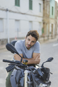 Portrait of young man sitting on motorbike - AFVF00154