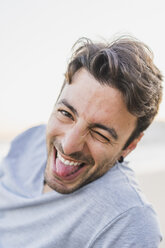 Portrait of winking young man stiking out tongue - AFVF00157