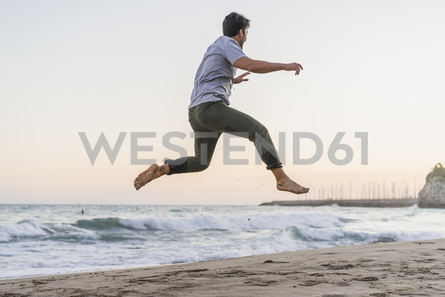 Happy young man jumping in the air on the beach at sunset - AFVF00160