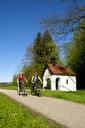 Germany, Bavaria, Upper Bavaria, Bad Heilbrunn, Antonius Chapel, cyclists - LBF01769