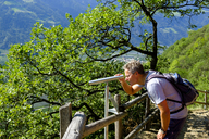 Italy, South Tyrol, Vinschgau, Naturns, Sonnenberg Panorama Trail, hiker looking through telescope - LBF01781
