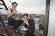 Two young men eating take out food on a fire escape - FSIF02654