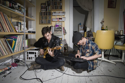 Two young men playing instruments in their living room - FSIF02657