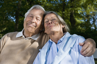A senior couple sitting on a bench together - FSIF02669