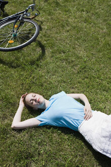 A young woman lying in grass near a bicycle - FSIF02693
