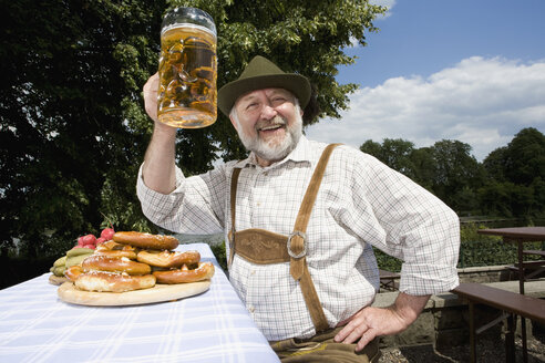 A traditionally clothed German man in a beer garden raising his beer glass in toast - FSIF02696