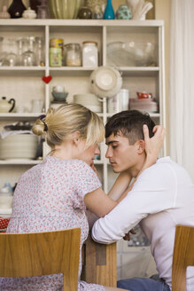 A young passionate couple sitting in a domestic kitchen - FSIF02723