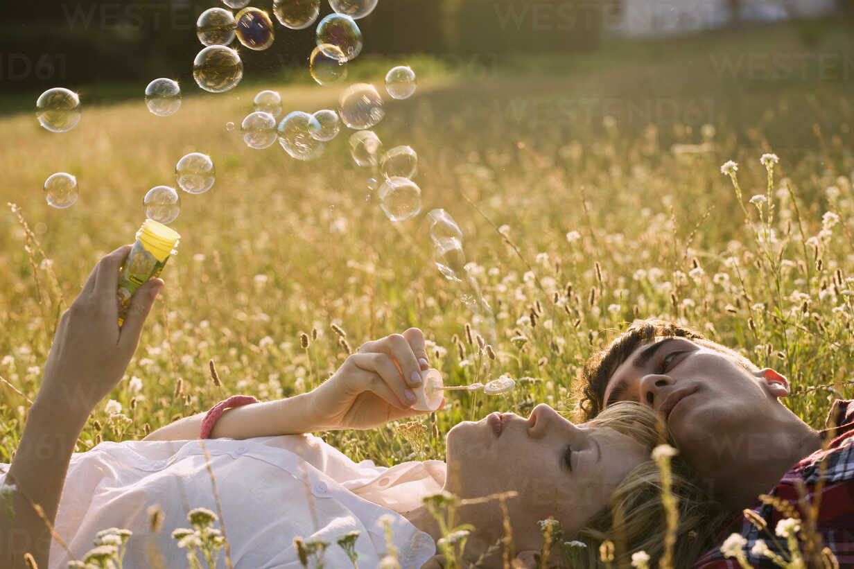 A young couple in a field blowing bubbles - FSIF02726 - fStop/Westend61