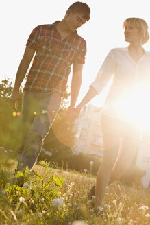 A young couple holding hands walking through a park, front view - FSIF02738