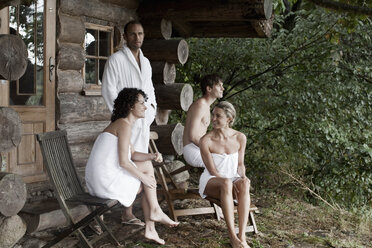 Four people relaxing outside the sauna at a health spa - FSIF02744